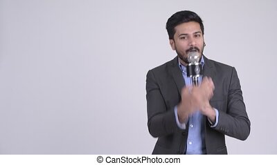 Young handsome bearded Indian businessman in suit against white background