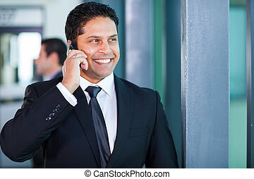 young indian businessman talking on mobile phone