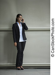 Young Indian businesswoman standing outside using mobile phone