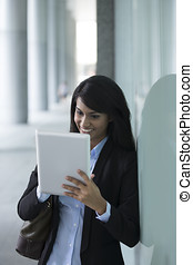 Young Indian businesswoman standing outside using Tablet PC