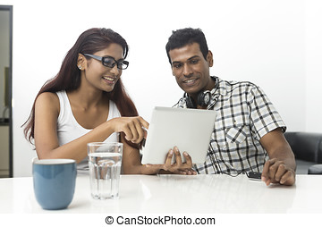 Young Indian couple using a digital tablet