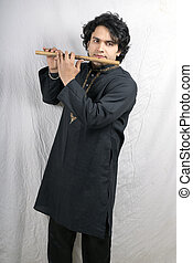 young indian male model in black kurta playing flute front...