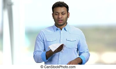 Young Indian man about to sneeze. Sneezing man on blurred background. Flu or allergy symptoms.