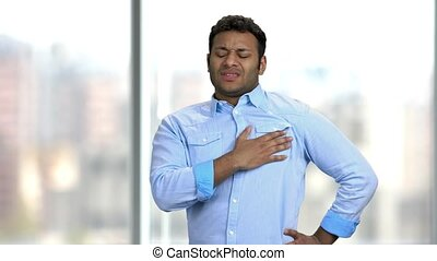 Young Indian man having chest pain. Unhappy middle-aged man suffering from heart ache on blurred background. Heart disease concept.