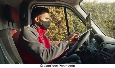Young indian man with cloth face mask using laptop in the van
