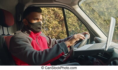 Young indian man with face mask using laptop in the van