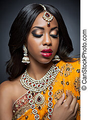 Young Indian woman in traditional clothing with bridal makeup and jewelry