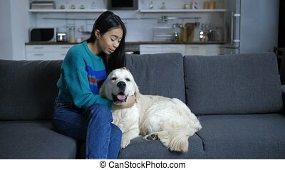 Young indian woman talking to dog at home - Smiling...