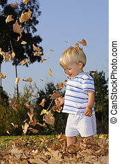 Young infant playing in falling leaves