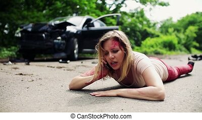 Young injured woman lying on the road after a car accident,...
