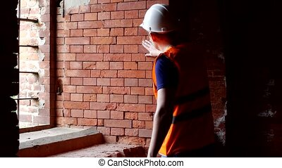 Young inspector checks the density of brick walls, preparation for reconstruction, architect