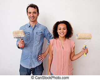 Young interracial couple painting the house wall together