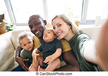 Young interracial family with little children taking selfie.