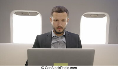 Young investor expert analyst businessman working with laptop, enjoying profitable transaction during flight in airplane.