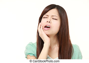 young Japanese woman suffers from toothache