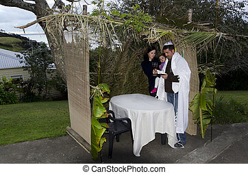 Young Jewish family prays at the Sukkah for the Jewish festival of Sukkot. A Sukkah is a temporary structure where meals are taken for the week.