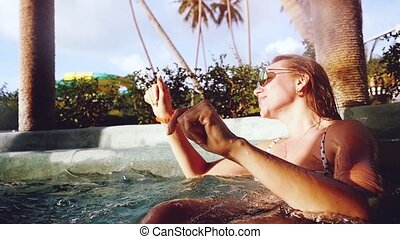 young jiyful woman in sunglasses relaxed in jacuzzi....