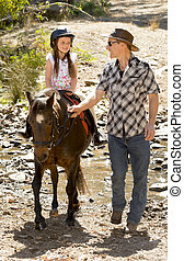 young jockey kid riding pony outdoors happy with father role as horse instructor in cowboy look