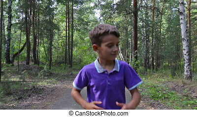 Cheerful boy having fun jogging on a summer day