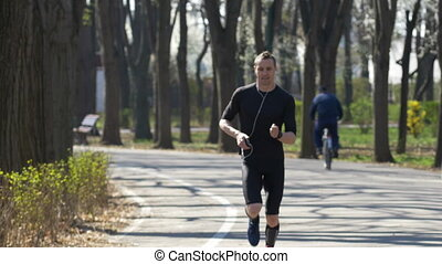 Young jogger listening to music with smartphone and hands...