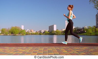 young jogger with red hair runs outdoors - redhead slim girl...