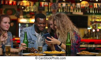 Young joyful people taking selfie with black smartphone,...