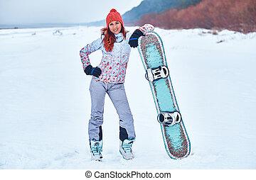Young joyful snowboarder woman smiling and posing