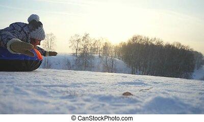 Young joyful woman tobogganing in the mountain through the sun in slow motion during beautiful sunset. 1920x1080