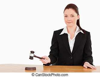 Young judge knocking a gavel smiling at the camera