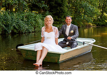 Young just married bride and groom on boat - beautiful young...