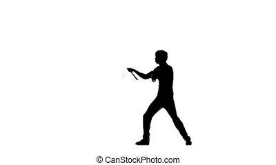 young karate or taekwondo man expertly twirling nunchaku,...
