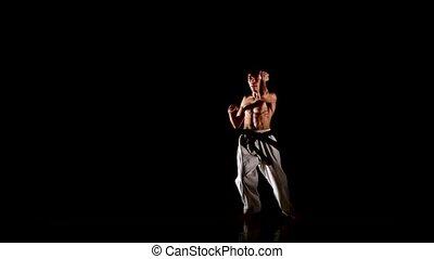young karate or taekwondo man jumping, high kick and fist...