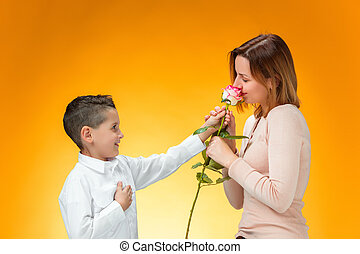Young kid giving red rose to his mom on orange background