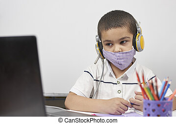 Young kid in headphones doing online exercises via laptop. Learning foreign language online or distance education, e-learning concepts