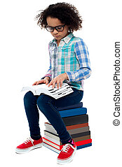 Young kid sitting on stack of books and reading