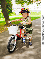 Young kid with injured knees is learning to ride a bike
