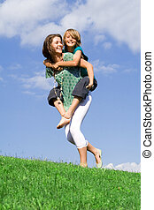 young kid with mother or sister playing piggyback