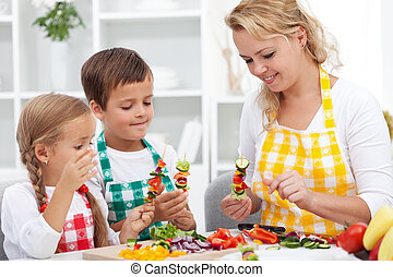 Young kids with their mother in the kitchen - preparing a vegetables snack