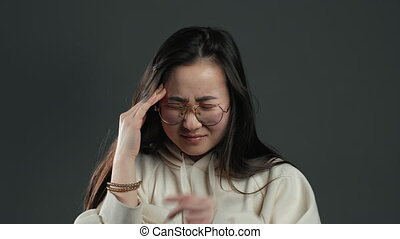Young korean asian woman with long hair having headache, studio portrait. Girl putting hands on head, isolated on grey background. Concept of problems and headache.