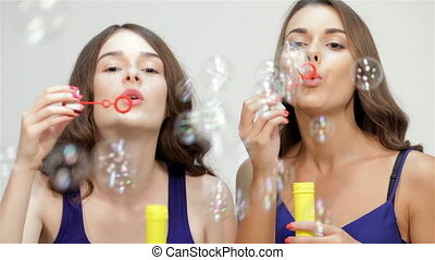 Young ladies blowing bubbles