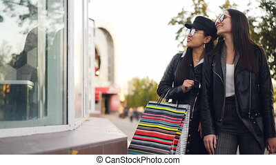Young ladies in fashionable clothes are walking along street, looking at shop-windows, talking and gesturing carrying shopping bags with purchases on autumn day.