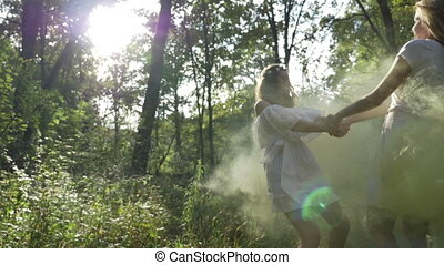 Young ladies that look like fairies holding hands and spinning in the wild forest covered in smoke