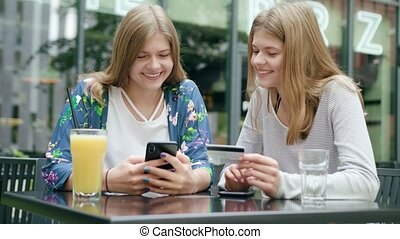 Young Ladies Using a Phone and Holding Credit Card
