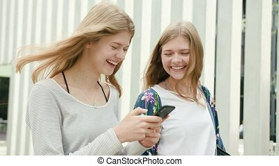 Young Ladies Using a Phone in Town