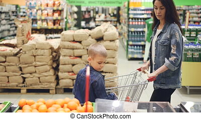 Young lady and her son in denim jackets are shopping together, they are walking through aisle in supermarket looking around and touching fruit. Shops and people concept.