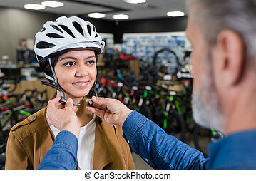 young lady being fitted with a bicycle helmet