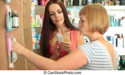 Young woman talking with shop assistant in the cosmetics department