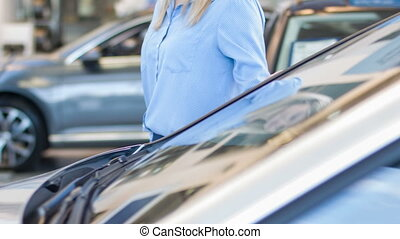 Young lady checking the car surface.