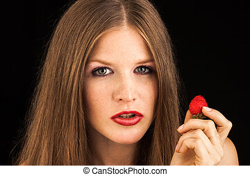 Young lady eating a strawberry