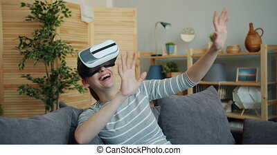 Young lady is enjoying new experience with augmented reality glasses sitting on sofa in flat laughing having fun. Technology, millennials and pastime concept.